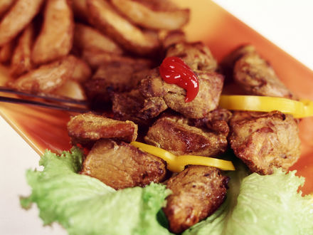 Обои Хрустящие кусочки шашлыка с кетчупом на салатных листьях, рядом горка картошки фри