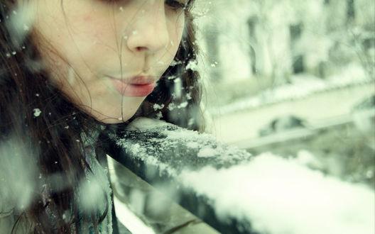 Обои Девушка сдувает снег с перил