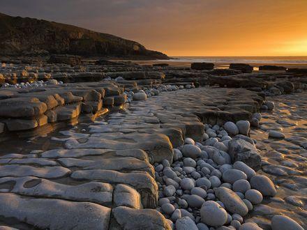 Обои Скалистый берег с камнями, до идеальной гладкости отполированными морской водой
