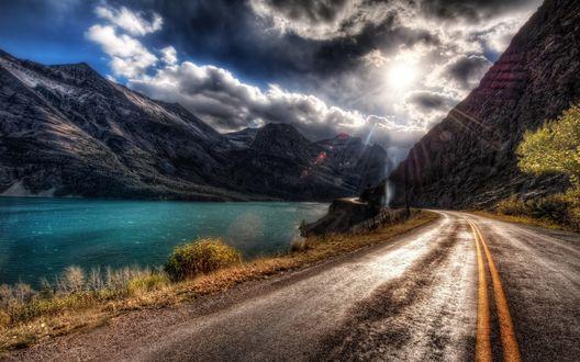 Обои Дорога проходит сквозь высокие горы вдоль лазурной реки