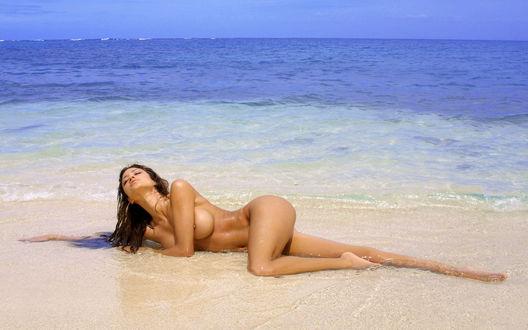 Обои Голая девушка принимает солнечные ванны на берегу моря