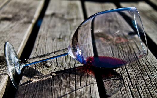 Обои Бокал с остатками вина лежит на полу из досок