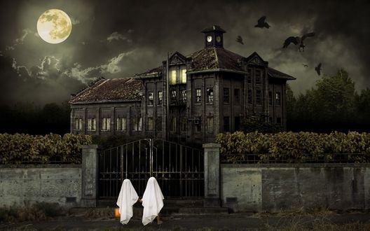 Обои Два ребенка нарядились привидениями и стоят у ворот мрачного замка