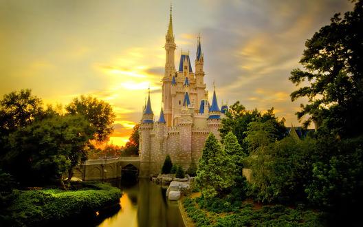 Обои Золотые лучи солнца прячутся за сказочными башнями замка Золушки, отражаясь в спокойной глади озера, окруженного густым лесом, Диснейленд, Париж, Франция