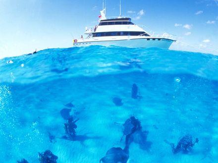 Обои Аквалангисты плавают в прозрачной воде под белой яхтой