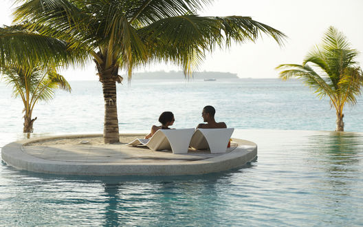 Обои Влюбленная пара отдыхает на шезлонгах посреди большого бассейна на берегу моря
