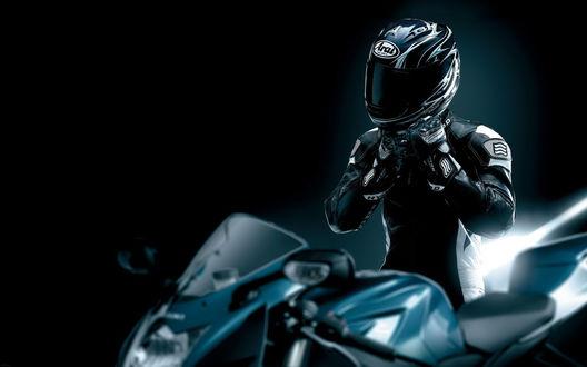 Обои Человек снимает шлем сидя на мотоцикле