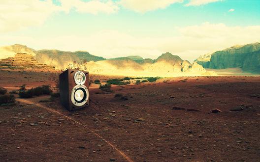 Обои В безлюдной пустыне стоит  одиноко колонка с динамиками, из которой музыкальные звуки выходят в виде ажурных  цветов