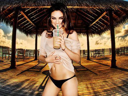 Обои Mila Kunis / Мила Кунис  с коктейлем стоит на фоне беседки на пляже