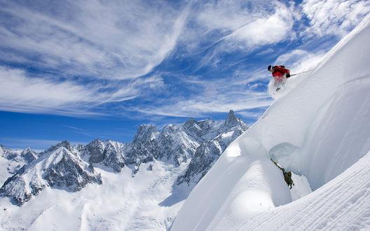 Обои Лыжник катается в заснеженных горах, небо над головой чистое и ясное