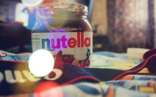 Обои Банка  nutella/нутеллы стоит на кровати, в фотографию попал шнурок от фотоаппарата Canon / Кенон