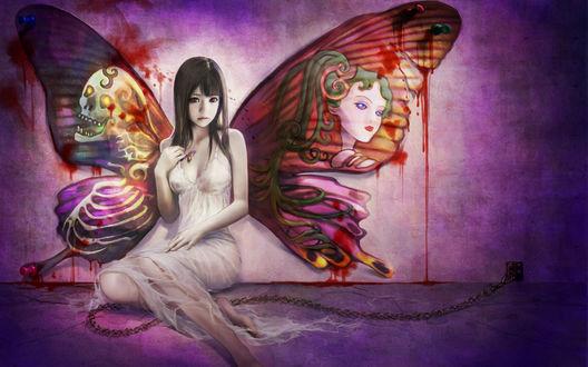 Обои Девушка с разрисованными крыльями бабочки за спиной (на одном крыле нарисована женщина с зелёными волосами, а на другом скелет, с горящими глазами) с разноцветной бабочкой в руке сидит у измазанной кровью стены прикованная к ней цепью