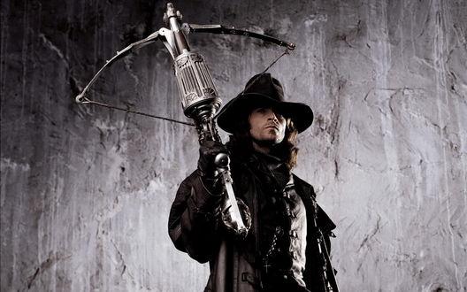 Обои Актер Хью Джекман / Hugh Jackman в роли Ван Хельсинга стоит у стены с арбалетом ( фильм *Ван Хельсинг / Van Helsing)
