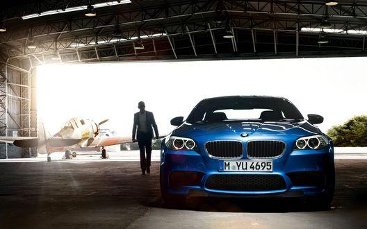 Обои Парень идёт от самолета  к синему БМВ / BMW