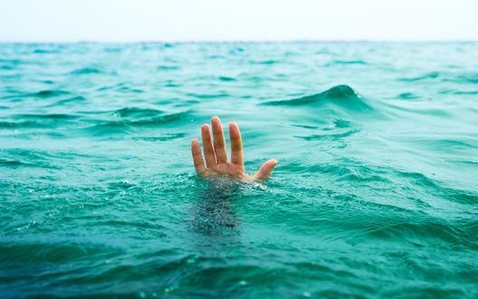 Обои Из моря видна рука человека