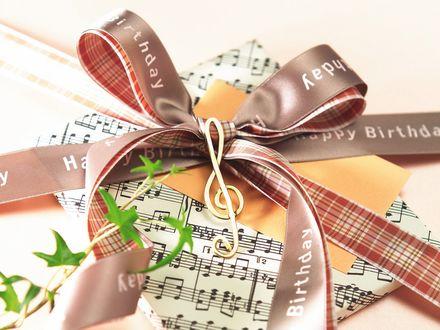 Обои Нотные листы, скрипичный ключ и записка, обвязанные лентой с надписью Happy Birthday / С днем рождения