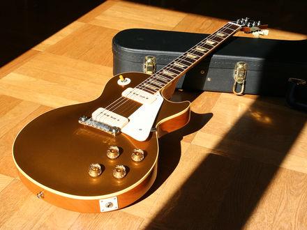 Обои Позолоченная гитара и чехол лежат на деревянном полу