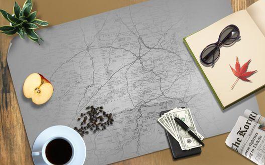 Обои На столе лежит карта, а на ней стоит чашка кофе, лежит яблоко, деньги, книга и очки, рассыпан кофе