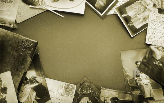 Обои Стол засыпан старыми фотографиями, только в центре есть немного места