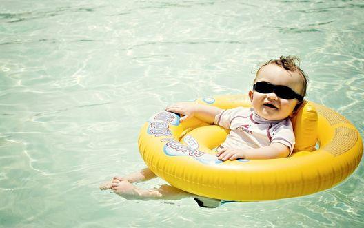 Обои Ребенок в очках плавает в бассейне на надувном круге