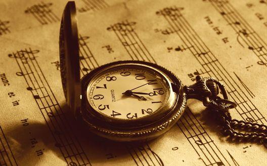 Обои Антикварные часы лежат на нотном листе