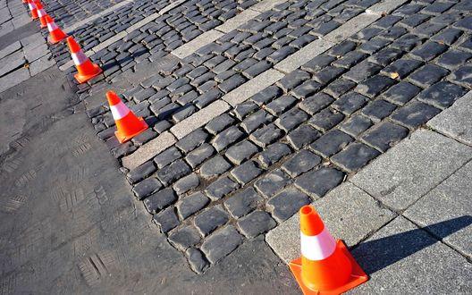 Обои Оранжевые конусы стоят на мощеной улице