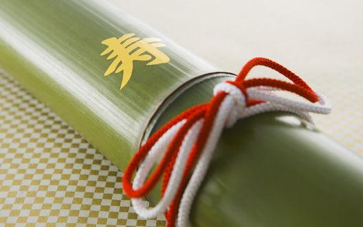 Обои Бамбуковая палочка с иероглифом и красно-белым шнурком в виде бантика