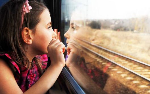 Обои Девочка смотрит в окно уезжающего поезда