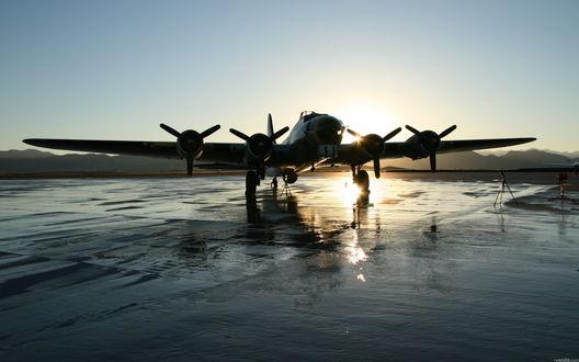 Обои Яркий солнечный свет освещает мокрую взлетную полосу и величественный самолет