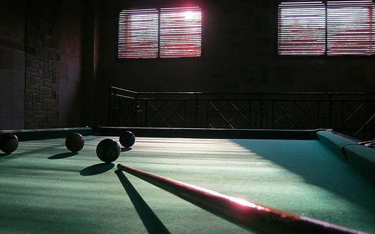 Обои Кий и шары на бильярдном столе в темной комнате