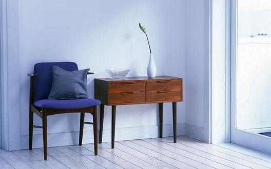 Обои В углу комнаты кресло и столик с белой вазой, в которой стоит веточка