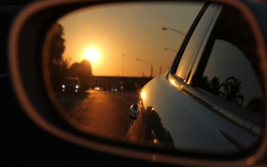 Обои Отражение дороги и заходящего над ней солнце в зеркале авто