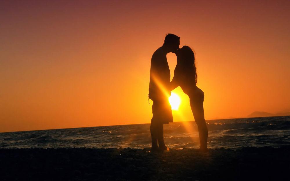 Парень целует девушку сидя на беме