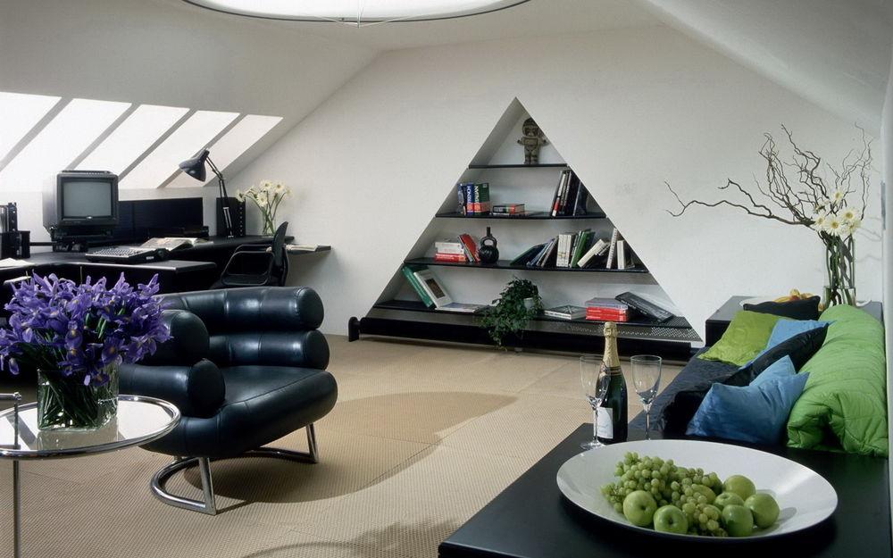 Обои для рабочего стола Гостиная комната в мансарде с треугольной нишей в стене для книг, на стеклянном столике свежие цветы, на другом столике шампанское и фрукты