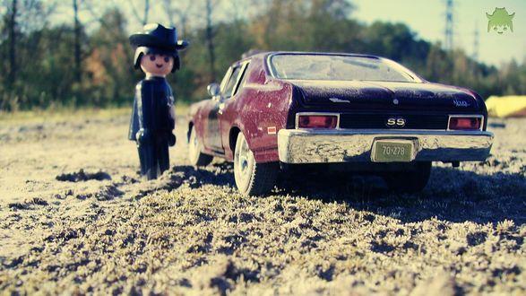 Обои Фигурка человечка в шляпе возле игрушечной машины на песке