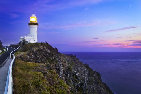 Обои Белый маяк вечером на утесе на фоне моря и заката