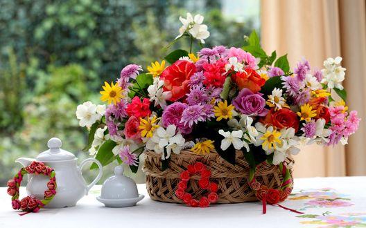 Обои Композиция из роз, жасмина, хризантем в плетеной корзине на столе, рядом стоит чайный сервиз