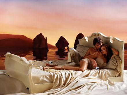 Обои Влюбленная пара лежит в постели на берегу моря, на заднем фоне розовеет закат