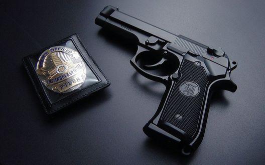 Обои Пистолет и полицейский жетон лежат на столе