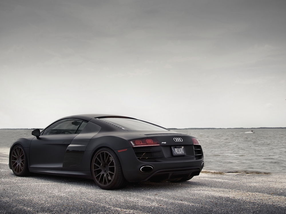 Обои для рабочего стола Черная Audi R8 стоит на песочном пляже