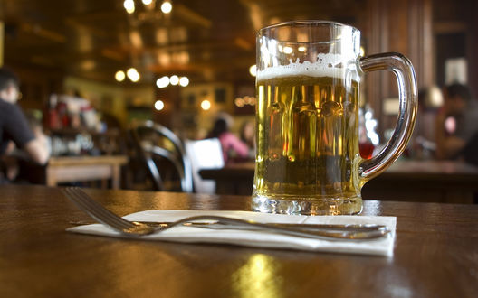 Обои Бокал пива и вилка на салфетке на столике в кафе