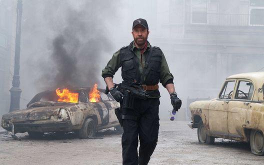 Обои Кадр из фильма 'Неудержимые 2' / 'The expendables 2', Чак Норрис / Chuck Norris с оружием на фоне горящей машины