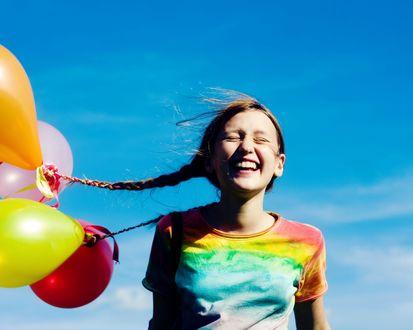 Обои Девочка, с шариками вплетенными в косички, жмурится и широко улыбается