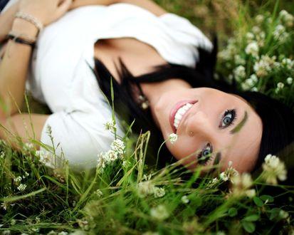 Обои Девушка лежит на траве и широко улыбается