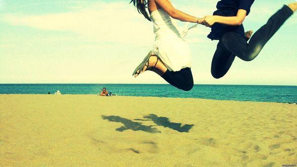 Обои Парень и девушка в прыжке на пляже