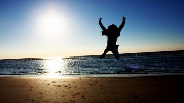 Обои Прыжок парня на песчаном берегу моря дарит позитив и хорошее настроение