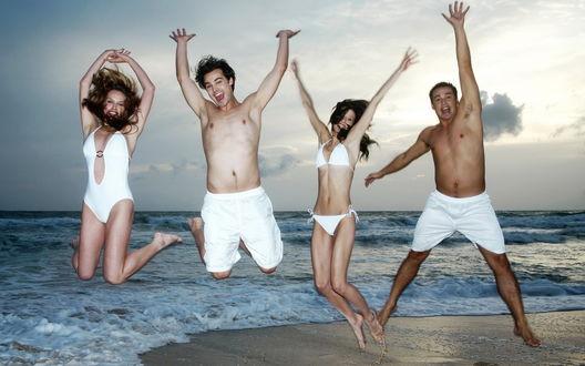 Обои Молодые люди отдыхающие на море прыгают в белых плавках и купальниках на берегу