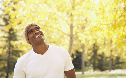 Обои Парень афро-американец в шапочке смотрит вверх улыбаясь