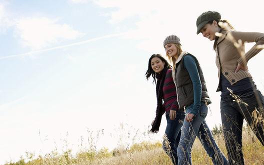 Обои Три девушки гуляют по полю, над ними по небу плывут облака