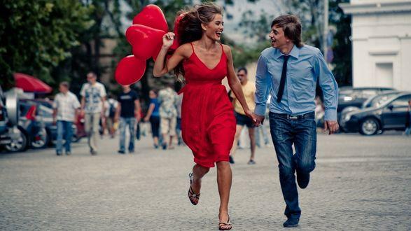 Обои Девушка держит в руке красные шары в виде сердец и бежит по площади с парнем